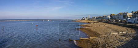 Foto de Kent, UK - February 21st 2019: A panoramic view from Herne Bay Pier in Kent, England.  The historic Clock Tower and Central Bandstand building can be seen in the distance. - Imagen libre de derechos
