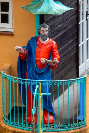 Photo pour Portmeirion, Wales - Sept 1st 2020:  A statue of Saint Peter located on the exterior of the Toll House in the village of Portmeirion in North Wales, UK. - image libre de droit