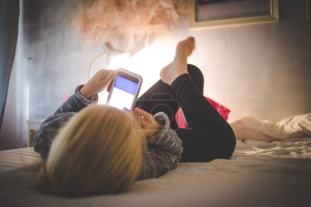 Beautiful blond toddler girl laying on her bed watching videos on a smart phone