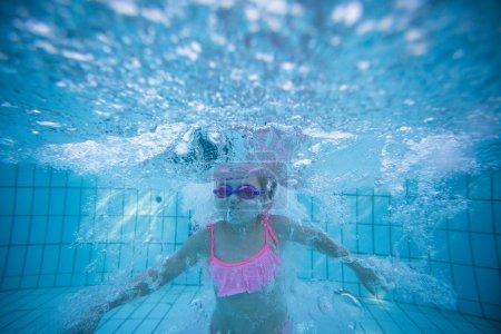 Photo pour Photo sous-marine grand angle d'une fillette nageant dans une grande piscine avec des lunettes et un bikini rose - image libre de droit