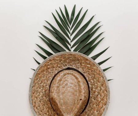 Flat lay summer composition. Creative concept tropical leaf and straw hat. Top view, copy space