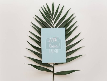 Flat lay summer composition. Creative concept tropical leaf and invitation card. Top view, copy space