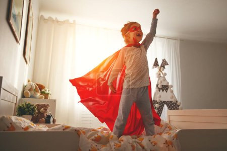 Photo for Child girl in a super hero costume with mask and red cloak  at hom - Royalty Free Image