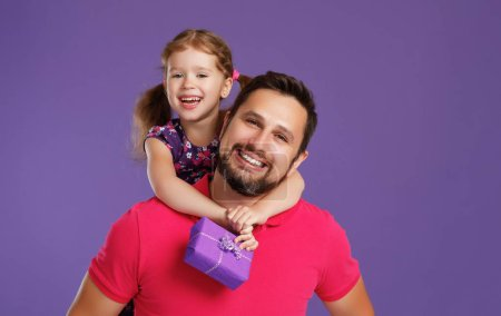 Photo for Happy father's day! cute dad and daughter hugging on colored violet backgroun - Royalty Free Image