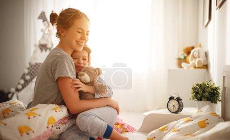 Foto de Despertar por la mañana. madre despierta a su hija en la cama de mornin - Imagen libre de derechos