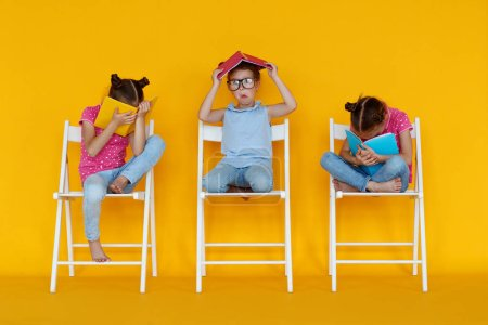Photo for Funny children girls read books on a colored yellow background - Royalty Free Image