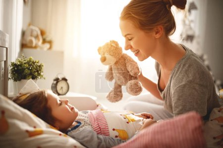 Photo for Morning awakening. mother wakes her daughter in bed in mornin - Royalty Free Image