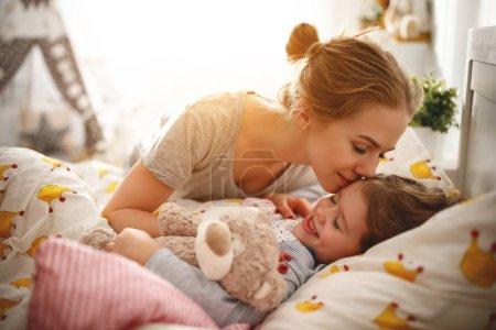 Photo pour Réveil matin. mère réveille sa fille dans son lit au matin - image libre de droit