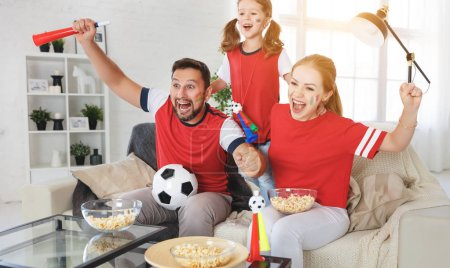 Photo for A family of fans watching a football match on TV at hom - Royalty Free Image