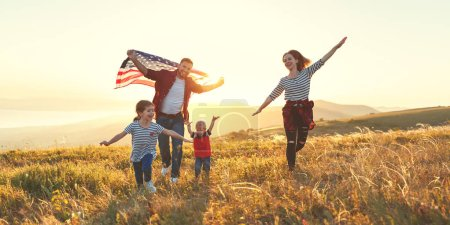 happy family with the flag of america USA at sunset outdoor