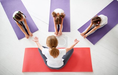 Photo for Children practicing are engaged in gymnastics and yoga with  teache - Royalty Free Image