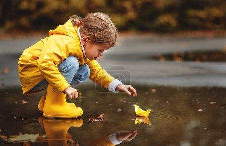 fröhliches Kindermädchen mit Regenschirm und Papierboot in einer Pfütze im Herbst auf dem Wasser
