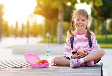 Photo pour Écolière enfant manger déjeuner pommes et bananes à l'école - image libre de droit