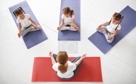 Photo for Children practicing are engaged in gymnastics and yoga with  teacher - Royalty Free Image