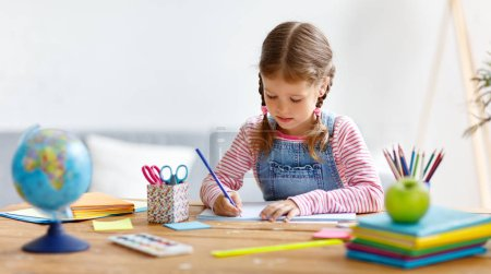 Photo for A child  girl  doing homework writing and reading at home - Royalty Free Image