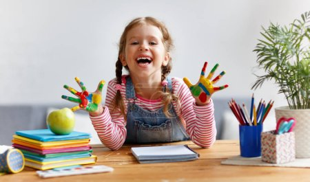 Photo for Happy funny child girl draws laughing shows hands dirty with pain - Royalty Free Image