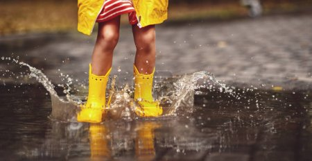 glückliches Kind in gelben Gummistiefeln in einer Pfütze auf einer Herbstwanderung
