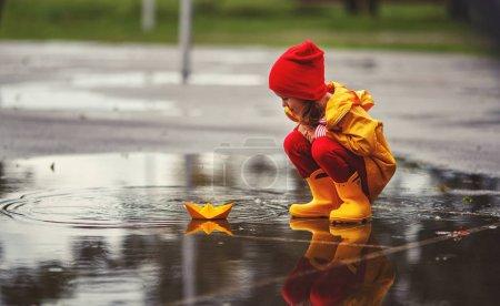 Foto de Muchacha del niño feliz con barco de papel y paraguas en un charco en otoño en natur - Imagen libre de derechos