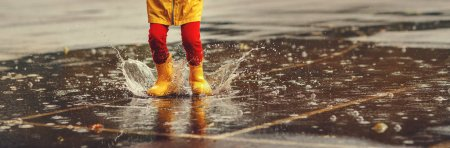 legs of child   with rubber boots jump in puddle on an autumn wal