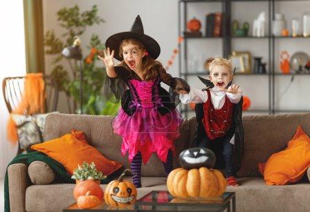 Photo pour Enfants heureux en costumes de sorcière et vampire préparer la maison pour les vacances Hallowee - image libre de droit