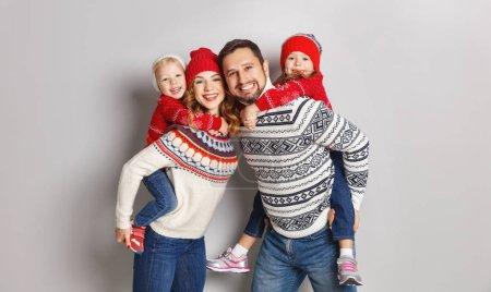 Photo pour Heureuse mère de famille, père et enfants en hiver chapeaux tricotés et chandails sur backgroun gris - image libre de droit