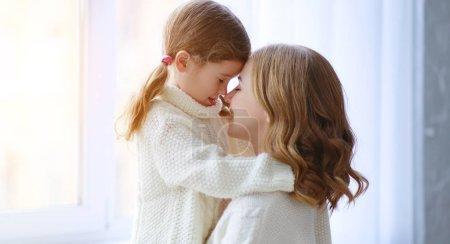 Photo pour Heureux aimant famille mère et enfant fille câlins par la fenêtre - image libre de droit