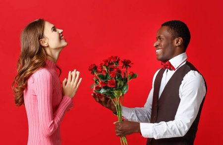Photo for Valentine's day concept. happy young couple with heart, flowers, gift on red backgroun - Royalty Free Image