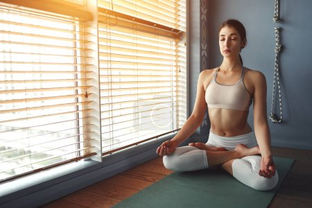 Photo for Young woman practices yoga at gym by the window - Royalty Free Image