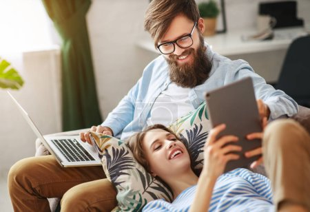 Photo for Happy family couple relaxing at home with laptop and table - Royalty Free Image