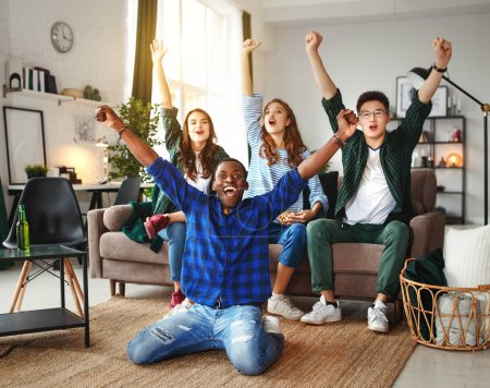 Photo for Group of happy young  friends fans watching a match on tv with beer and pizza at hom - Royalty Free Image