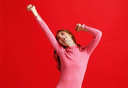 Foto de Joven hermosa chica emocional en vestido rosa sobre fondo rojo - Imagen libre de derechos