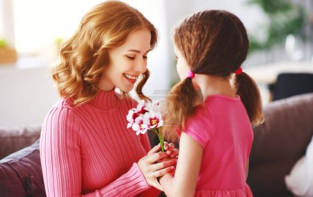 Photo for Happy mother's day! child daughter congratulates mother and gives a bouquet of flowers to tulips and postcar - Royalty Free Image