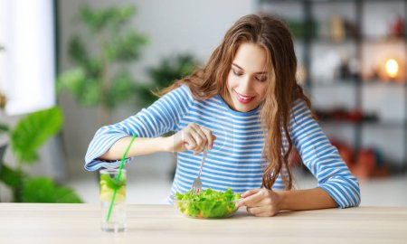 Photo for Healthy eating. happy young girl eating salad in the morning in kitche - Royalty Free Image