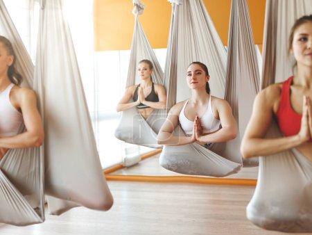 Photo pour Un groupe de personnes engagées dans une classe d'yoga Aero en hamacs antigravit - image libre de droit