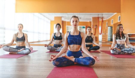 Photo for A group of people engaged in yoga class meditate in Lotus positio - Royalty Free Image