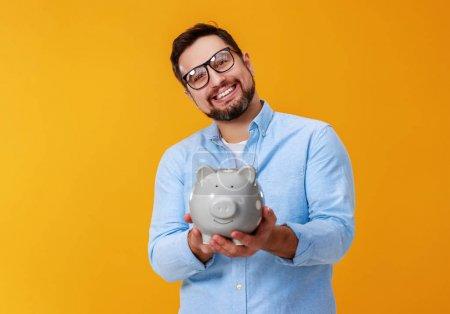 Photo pour Concept de finance et d'affaires. homme avec la tirelire sur un colo jaune de fond - image libre de droit