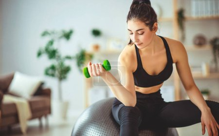 Photo for A young woman doing fitness and sports at home - Royalty Free Image