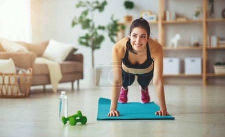 Photo pour Une jeune femme faisant de fitness et sport à la maison - image libre de droit