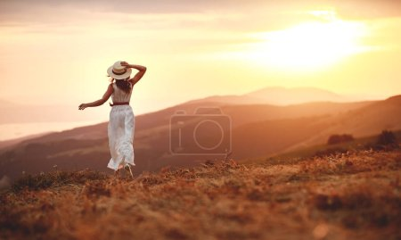 Photo for Happy woman standing with her back on the sunset in nature in summer with open hand - Royalty Free Image