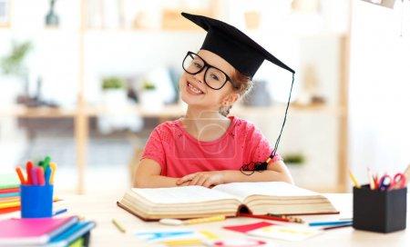 Photo pour Une fille enfant drôle faisant des devoirs d'écriture et de lecture à la maison - image libre de droit