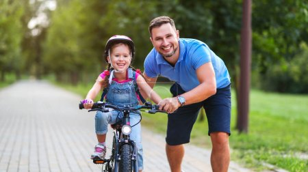 Photo for Happy family father teaches child daughter to ride a bike in the Park in natur - Royalty Free Image