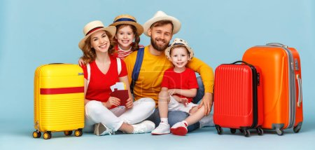 Photo for Full body happy parents and children with luggage, passports and tickets smiling and looking at camera against blue backdro - Royalty Free Image