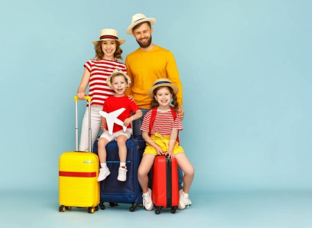 Full body happy family parents and children with luggage smiling and looking at camera against blue backdro