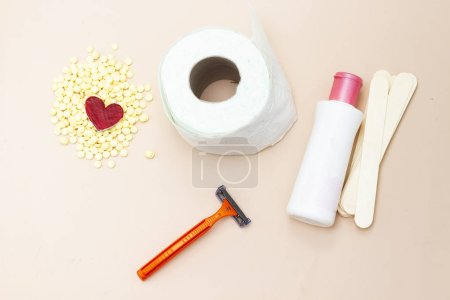 Personal hygiene : Toilet paper roll and yellow wax, wooden stick, shaver and intimate lotion