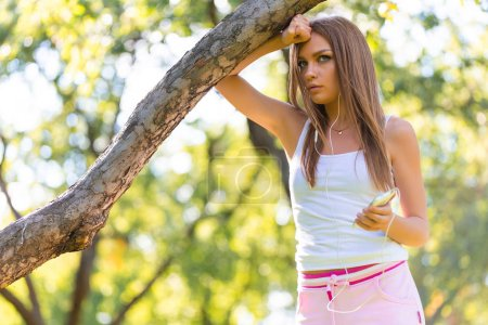 Young girl relaxing after jogging. She is using he...