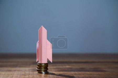 Photo pour Concept d'entreprise, de finance, d'investissement, d'épargne et de bourse. Une fusée en papier décollant d'une pile de pièces . - image libre de droit