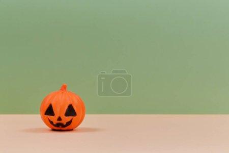 Photo pour Décoration de citrouille en plastique avec visage effrayant. Halloween et concept de vacances d'automne. Espace de copie. Isolé sur fond vert . - image libre de droit