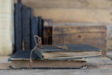 Photo pour Livres anciens et une boîte en bois sur une étagère. Anciennes maisons d'édition côte à côte sur une table en bois. Fond sombre . - image libre de droit