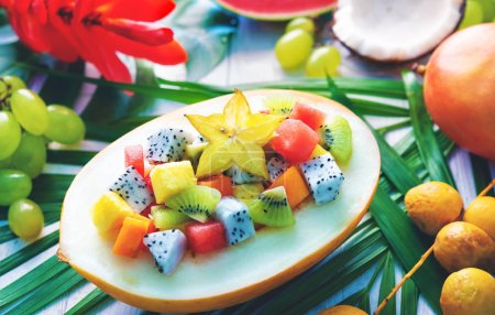 Exotic tropical fruits salad served in half a melon on leaves of palm trees