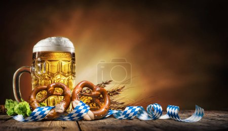 Oktoberfest beer with pretzel, wheat and hops on w...